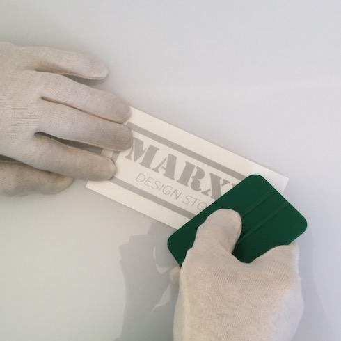 Aufkleber anbringen: Aufkleber mit der Sichtseite nach oben fest anreiben
