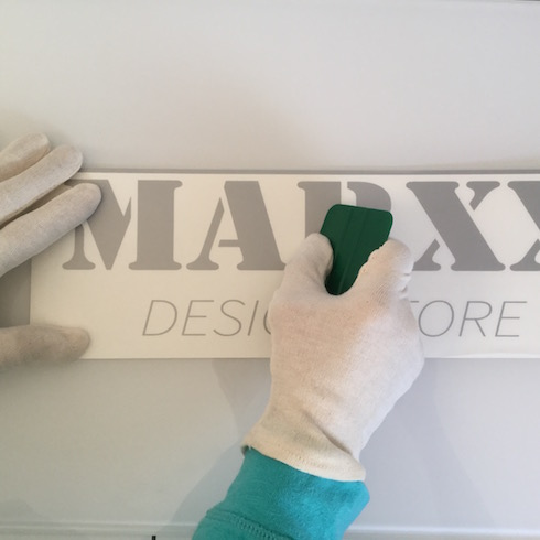 Wanddekor anbringen: Mit Rakel Trägerfolie fest aufreiben